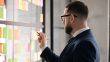 Serious Middle-aged Businessman In Glasses Brainstorm Engaged In Creative Thinking In Office, Concentrated Male Employee Write On Colorful Sticky Notes Develop Business Project At Workplace