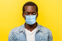 Portrait Of Silly Crazy Man With Surgical Medical Mask Crossing Eyes Looking At His Nose, Fooling Around And He Stay Crazy Of News About Quarantine. Indoor Studio Shot Isolated On Yellow Background