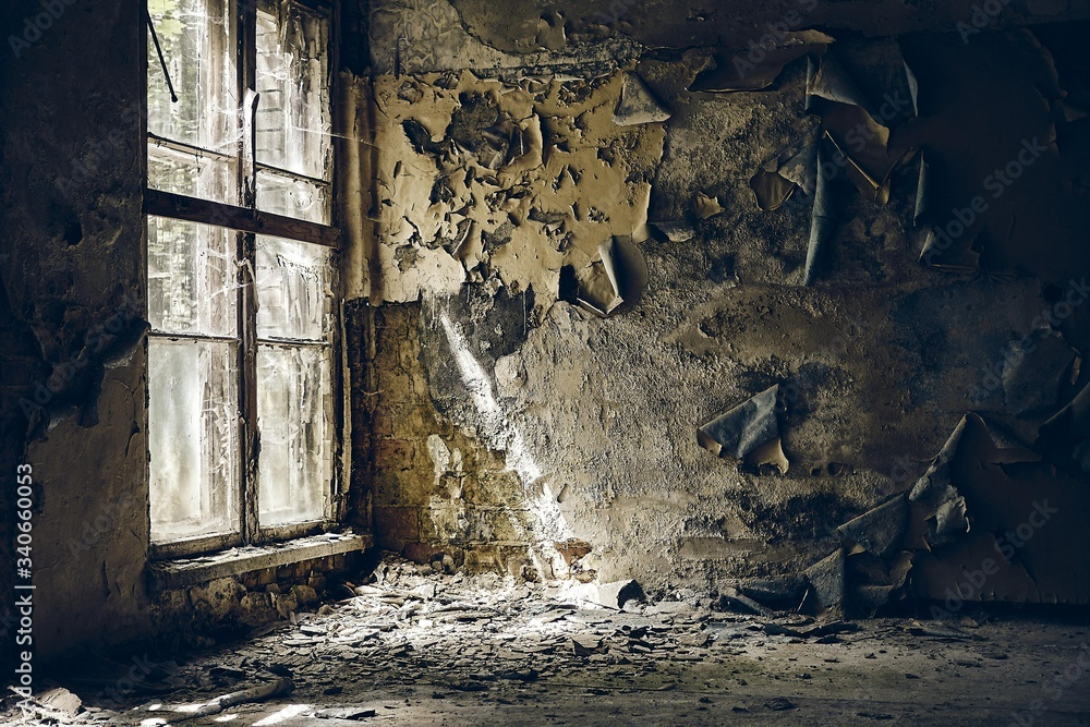 Fototapeta Ruined walls of an abandoned building under the sunlight coming from the broken window