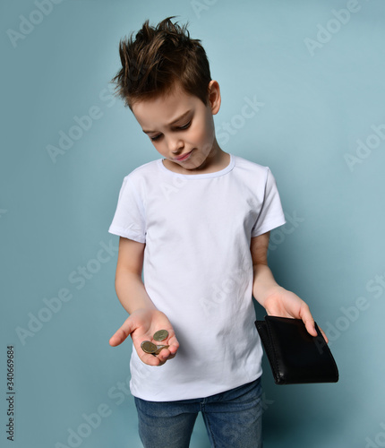 Obraz na plátně Little boy in white t-shirt showing empty wallet and coins on pastel blue background