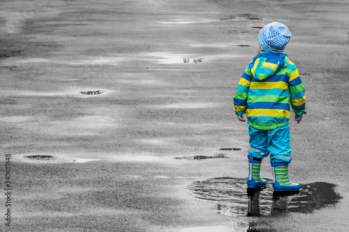 Obraz na płótnie Rear View Of Child Wearing Raincoat While Standing On Puddle During Rainy Season
