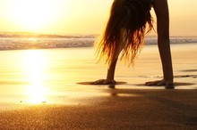 Woman Exercising On Sand At Beach