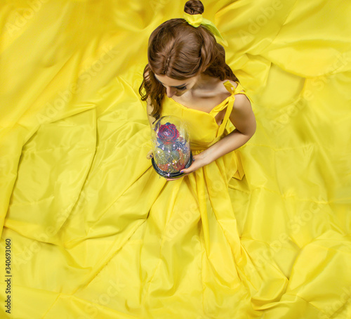 Fotografie, Obraz Pretty woman in the yellow long dress closeup with red rose in her hands