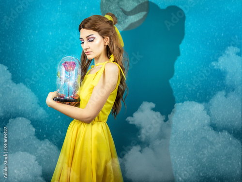 Fototapeta Woman in the yellow dress with red rose in her hands on the background of the beast