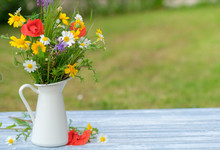 Wild Flower Bouquet In White Jug On Blue Vintage Wooden Table. Still Life With Bouquet Of Spring Wildflowers. Summer Day. Beautiful Floral Background. Copy Space.