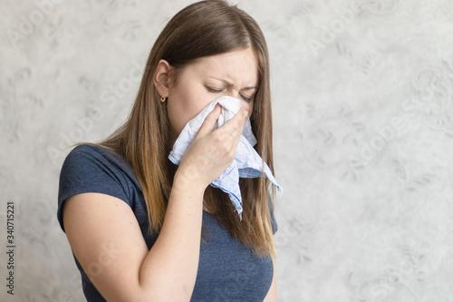 Murais de parede Sick woman with handkerchief sitting at home with flue, virus, cold, seasonal allergy symptom