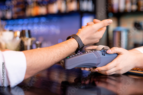 Fototapeta Young client with smartwatch keeping his wrist over payment machine obraz