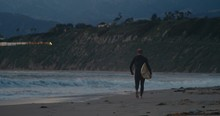 Surfer Walking On Beach At Sunset As Freight Train Passes By On Hills Above - Slow Motion