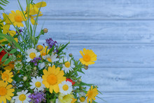 Close Up Of Mixed Colorful Wildflowers On Blue Vintage Wooden Background. Top View On Still Life With Bouquet Of Spring Wild Flowers. Spring Or Summer Cute Floral Backdrop With Copy Space.