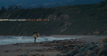 Surfer Walking On Beach During Sunset As Freight Train Passes By On Hills Above Wide Shot - Slow Motion