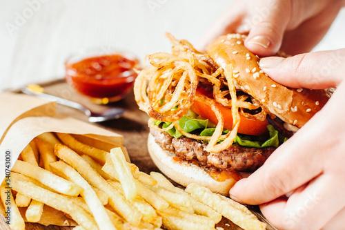Fototapeta Fast food. Traditional American cuisine. Burger in female hands. French fries bbq sauce. obraz