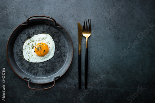 Fototapeta Homemade fried egg in a vintage pan and stylish cutlery on a dark background. View from above. Copy space for text. obraz