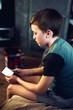 Portrait of a pensive unhappy boy with a smartphone in the room. A teenager with a mobile phone looks at a white screen. View messages, play, learn online, video conference. Horizontal image