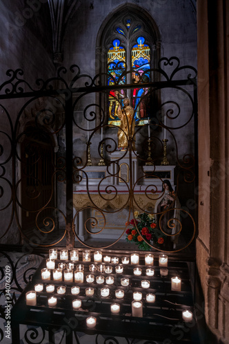 Photo church window with stained glass and candles in the foreground