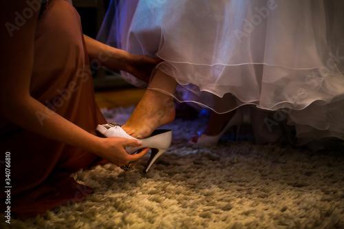 Photo Mulher colocando o sapato branco de uma noiva no dia do seu casamento