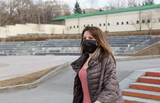 Woman of European appearance in a black medical mask on her face from coronavirus looks at the background of empty Grod and stre