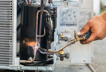Close Up Of Air Conditioning Repair Use Fuel Gases And Oxygen To Weld Or Cut Metals, Oxy-fuel Welding And Oxy-fuel Cutting Processes, Repairman On The Floor Fixing Air Conditioning System