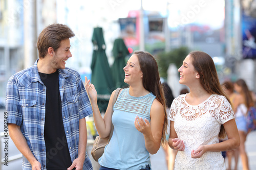 Happy friends laughing and talking in the street Wallpaper Mural