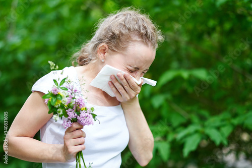 Pollen allergy, womansneezing with bouquet of flowers Canvas Print