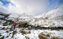 A Hiker Crossing Glenridding Beck Over A Wooden Bridge On Route To A Snow Covered Catstye Cam And Helvellyn In The English Lake District.