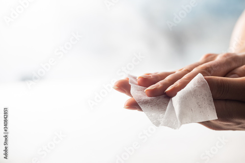 Woman cleaning her hands with wet wipe on a white backgrounds Fototapete