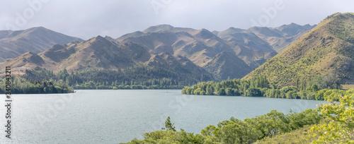 Photo green shore and barren slopes at Aviemore lake, New Zealand