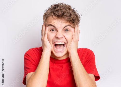 Portrait of surprised teen boy, on gray background Wallpaper Mural