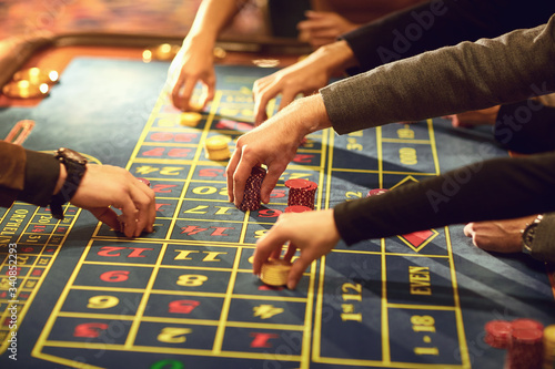 Close-up of hands with chips for gambling on a casino roulette table Obraz na płótnie