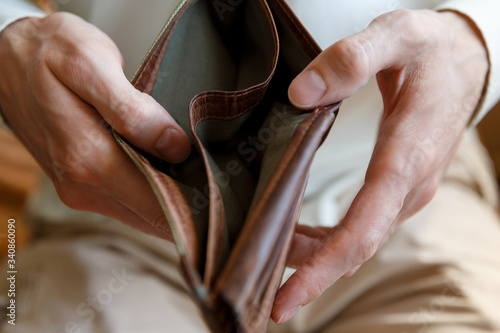 Photo Empty wallet in the hands of a man on a plain background