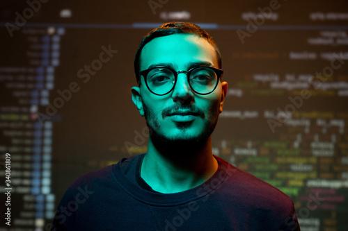 Fototapeta Portrait of serious young Arabian programmer in eyeglasses standing against coding background obraz