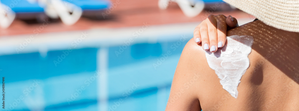 Fototapeta Woman in hat is applying sun cream on her shoulder by the pool. Sun Protection Factor in vacation, concept
