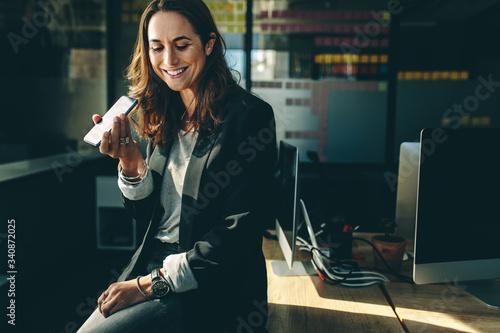 Obraz Female executive talking on speaker phone - fototapety do salonu
