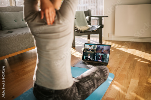 Fitness coach teaching yoga online to group of people Fototapete