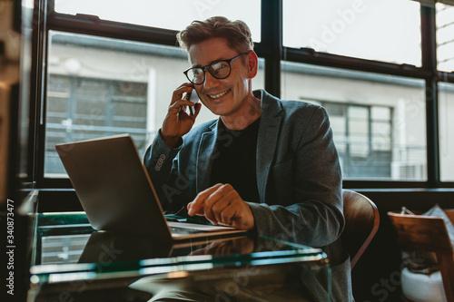 Fototapeta Corporate professional sitting making a phone call