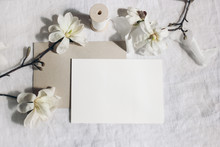 Wedding Stationery Mock-up Scene. Blank Horizontal Greeting Card, Envelope On Linen Tablecloth Background. White Magnolia Stellata Tree Branches And Ribbon In Sun. Feminine Still Life. Flat Lay, Top