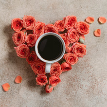 Cup Of Black Coffee Surrounded With Fresh Coral Mini Roses On A Textured Beige Background.