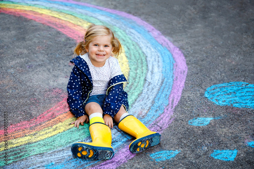 Happy little toddler girl in rubber boots with rainbow painted with colorful chalks on ground during pandemic coronavirus quarantine Canvas Print