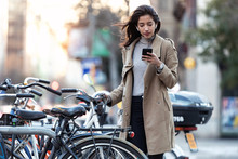 Pretty Young Woman Consulting The Map On Her Mobile Phone Before Taking The Bicycle On The Street.