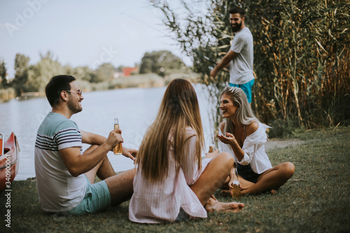 Fotografia Group of young friends enjoying the nature on the lakeside