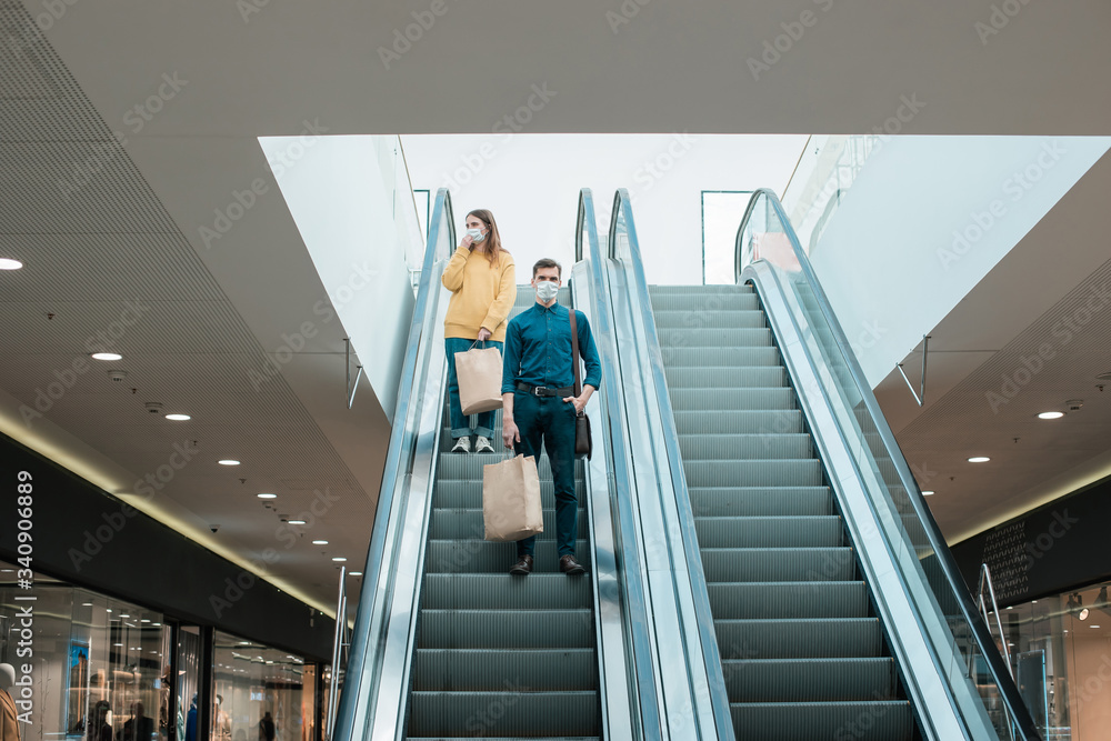 Fototapeta young man in a protective mask standing on an escalator in a shopping center