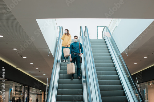 young man in a protective mask standing on an escalator in a shopping center Wallpaper Mural