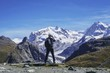 Rear View Of Man Photographing Snowcapped Mountains Against Sky