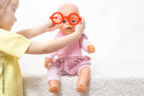Fototapeta The child plays with a doll and puts on toy glasses