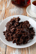 Close Up Of Corn Flakes Cookies, Coated In Dark Chocolate, With A Cup Of Black Tea On Old Wooden Table