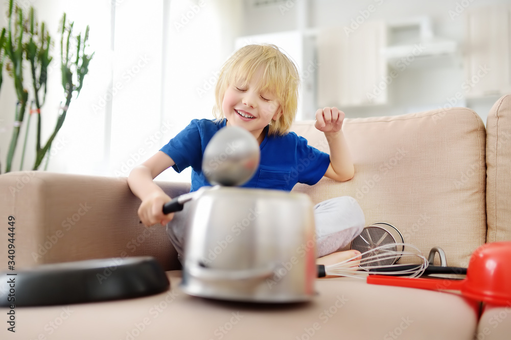 Fototapeta Mischievous preschooler boy play the music using kitchen tools and utensils at home during quarantine. Funny drum part from child. Entertainment a kids at home.