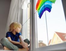 Little Boy Sitting At Window W...