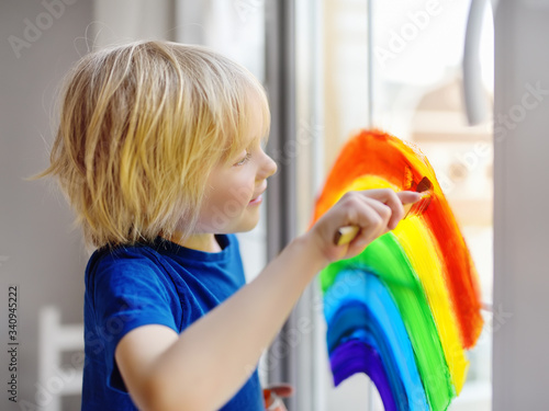 Obraz Little boy drawing on window rainbow while coronavirus quarantine. Rainbow sign is symbol of hope, means that everything will be OK. - fototapety do salonu