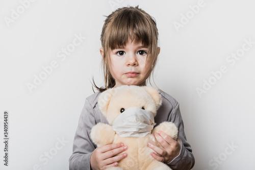 Uen petite fille tenant son ours en peluche avec un masque pendant la période du Tapéta, Fotótapéta