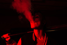Contemporary Female In Bomber Jacket Holding A Black Baseball Bat On Shoulder While Smoking With Red Light On Background