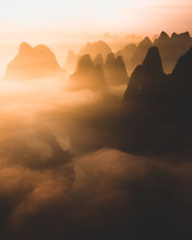 Silhouettes Of Big Tall Mountains Against Bright Cloudy Sky On Foggy Morning In Guilin